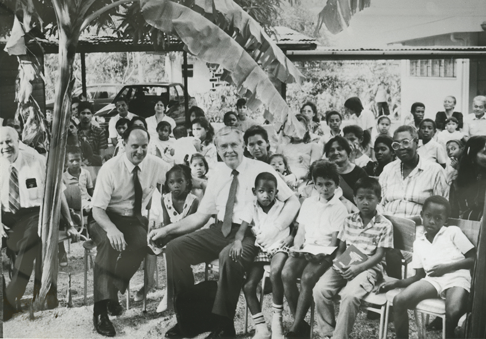 Elder Charles Didier and Elder M. Russell Ballard, on front row, mingle with children and others in the congregation when Suriname was dedicated for the preaching of the gospel in February 1990.