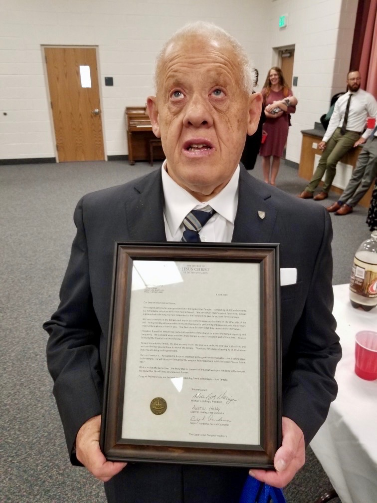 Dennis Preece holds a framed letter from the Ogden Temple presidency recognizing him for reaching 13,000 endowments performed in June 2019.