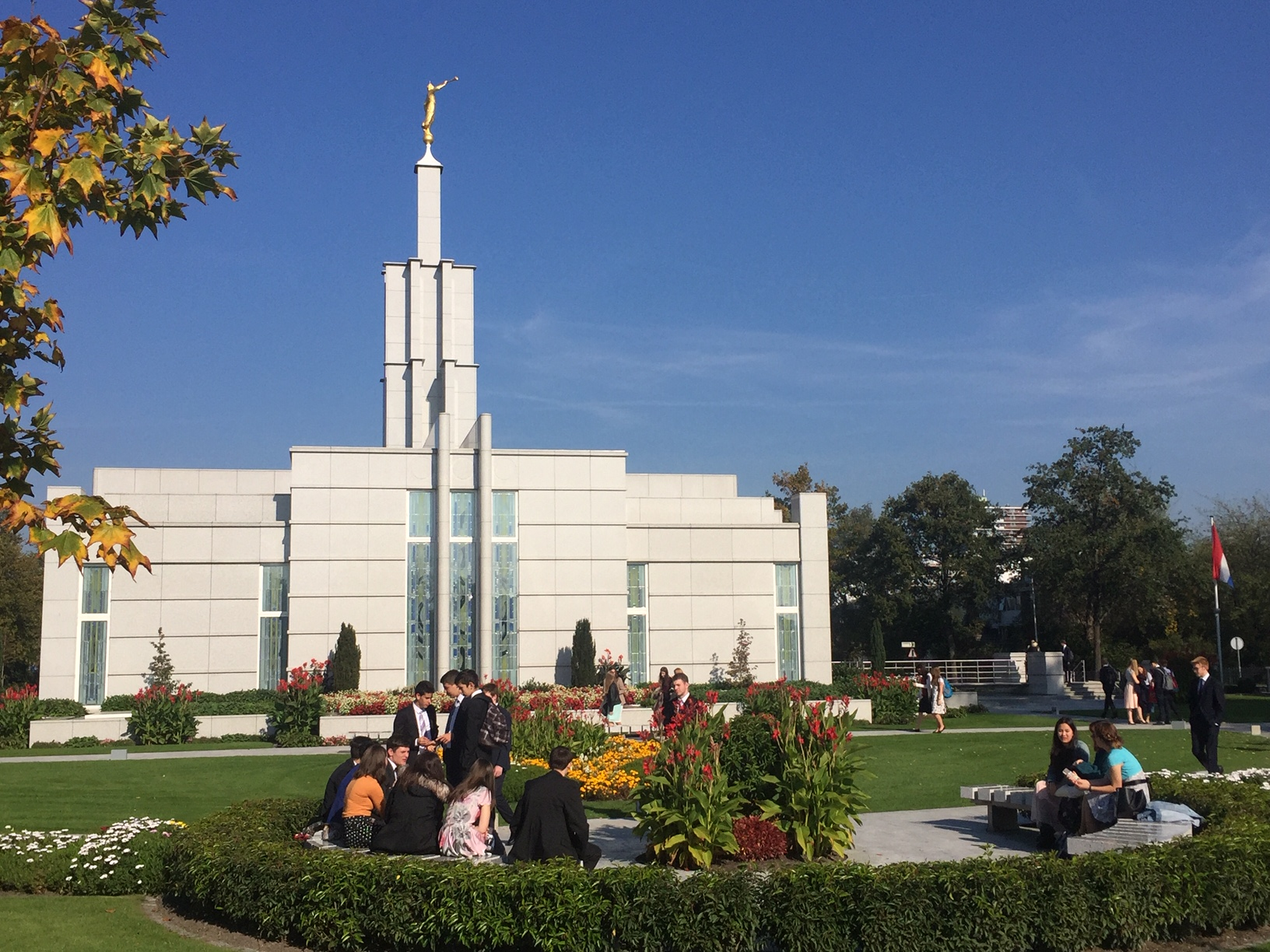 Youth from the Friedrichsdorf Germany Stake sit on the grounds outside The Hague Netherlands Temple during the stake's October 2018 temple trip.