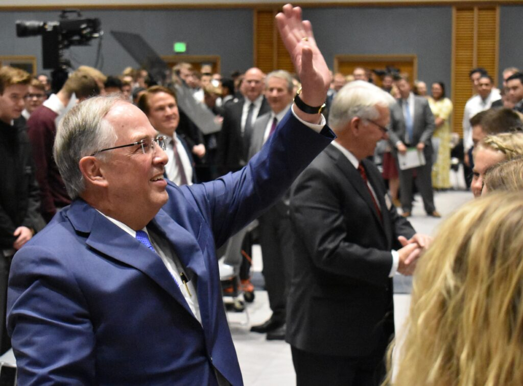 Elder Neil L. Andersen of the Quorum of the Twelve Apostles waves to missionaries seated higher up in the auditorium following a Thanksgiving Day devotional at the Provo Missionary Training Center on Nov. 28, 2019, in Provo, Utah.