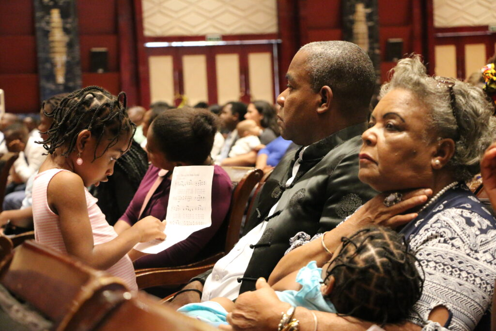 A family listens to Elder Jeffrey R. Holland of the Quorum of the Twelve Apostles speak during a multi-stake conference at the Joaquim Chissano International Conference Center in Maputo, Mozambique, on Sunday, Nov. 17, 2019.