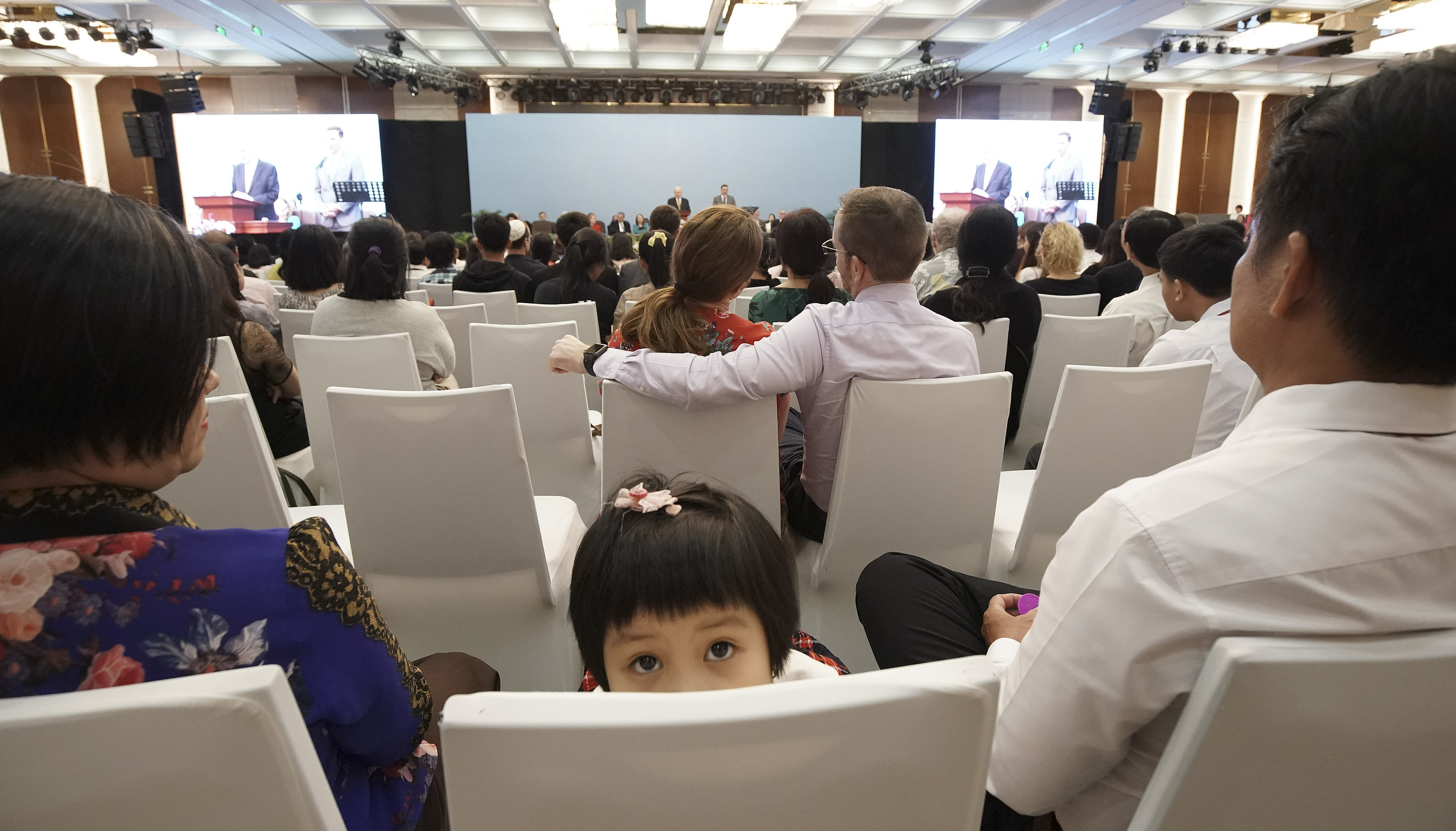 A young attendee looks around as President Russell M. Nelson of The Church of Jesus Christ of Latter-day Saints and his wife, Sister Wendy Nelson, speak during a devotional in Ho Chi Minh City, Vietnam, on Nov. 18, 2019.
