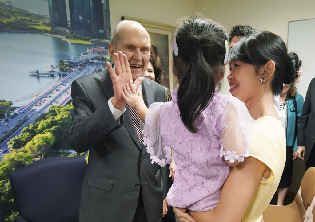 President Russell M. Nelson of The Church of Jesus Christ of Latter-day Saints high fives Danielle Lim, 3, while meeting with a three-generation family in Singapore on Nov. 20, 2019.