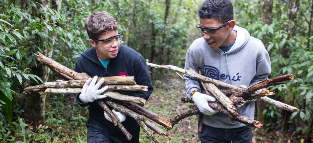 Young men carry sticks during a camping trip.