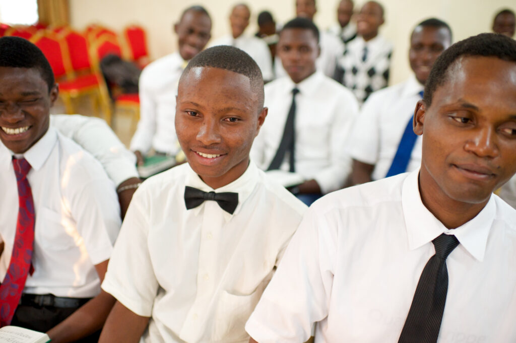A group of young men in the Democratic Republic of the Congo smile during a quorum meeting.