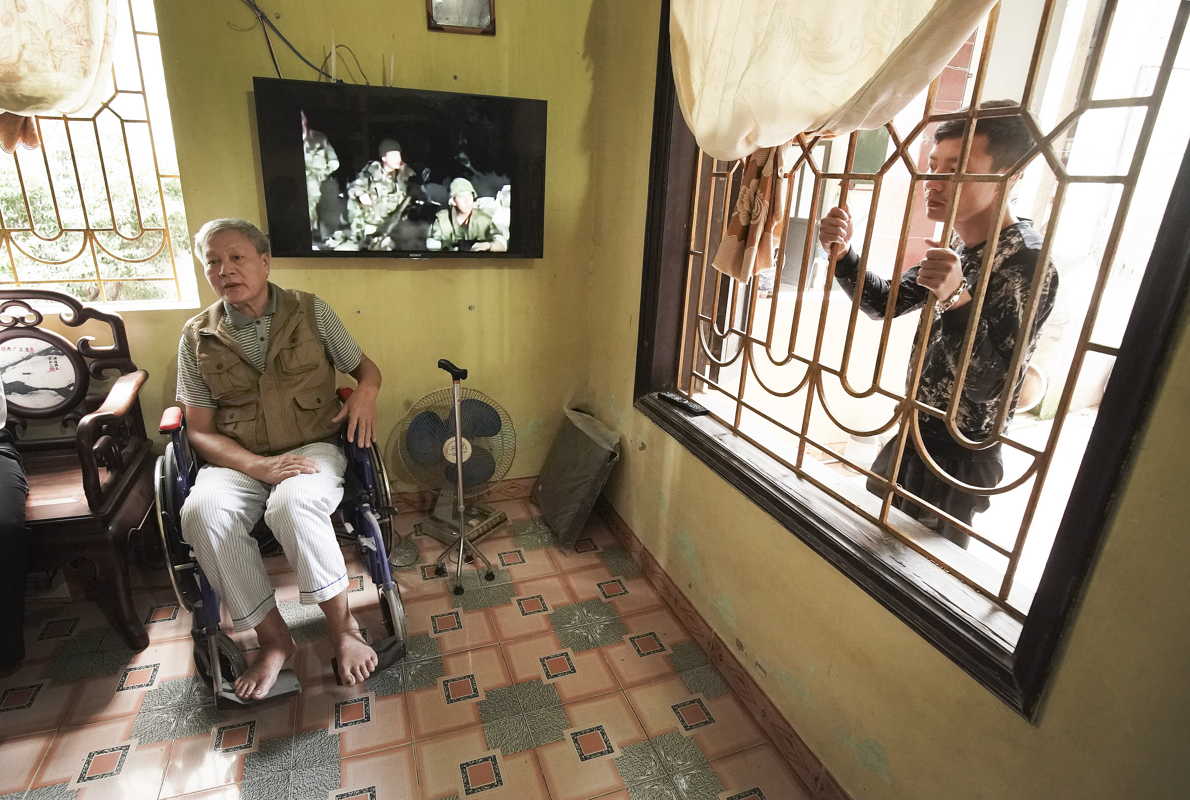 Tai Quang Pham sits in his wheelchair given to him by Latter-day Saints Charities in Hanoi, Vietnam on Saturday, Nov. 16, 2019. His son Mai Thi Pham looks through the window.