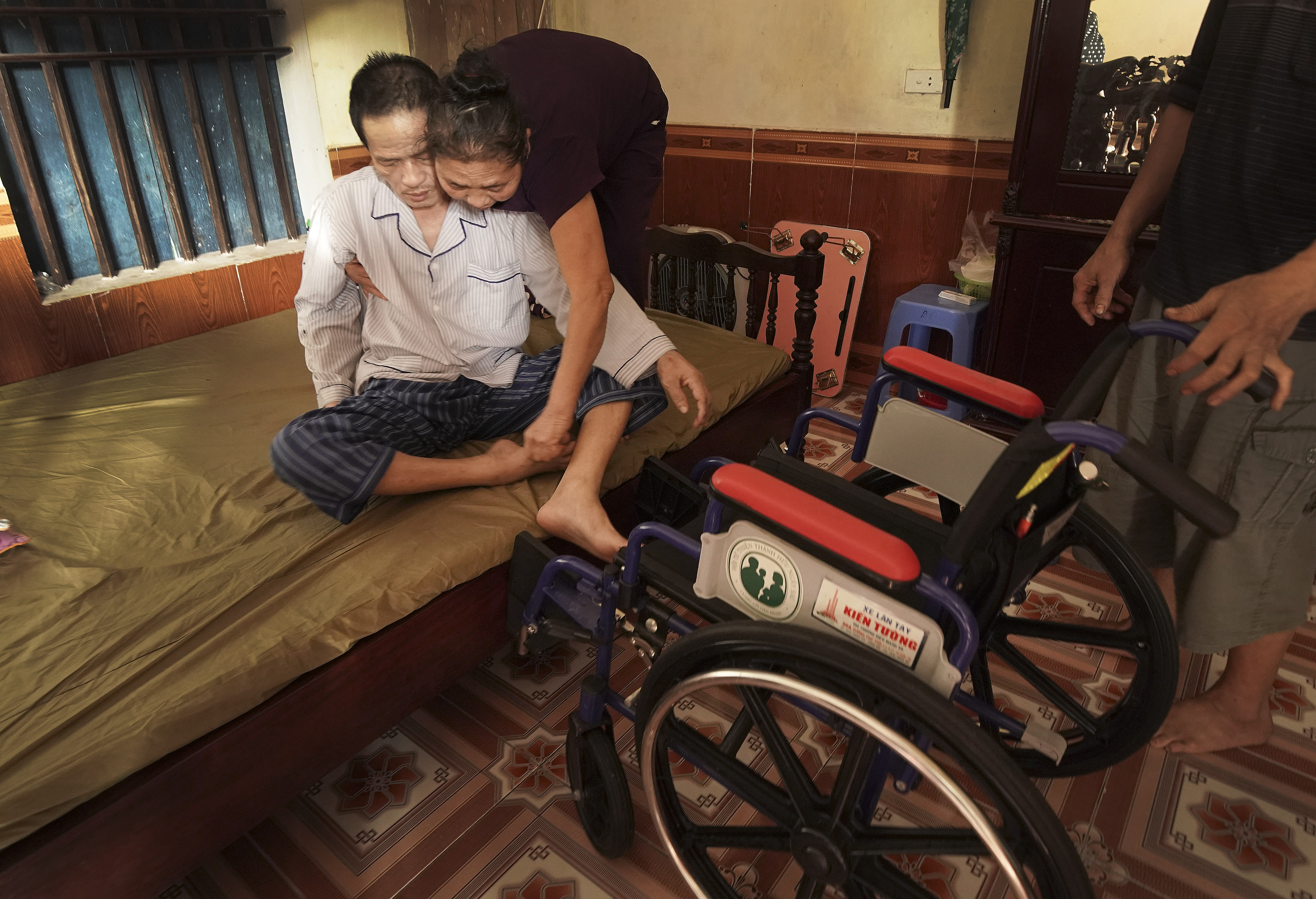 Bao Dinh Tran is helped by his wife Quyen Thi Mai into his wheelchair given to him by Latter-day Saints Charities in Hanoi, Vietnam on Saturday, Nov. 16, 2019.