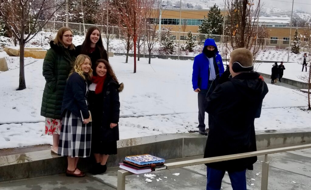An elder takes a photo of four sister missionaries on the Provo Missionary Training Center campus on Christmas Day, 2019, in Provo, Utah.