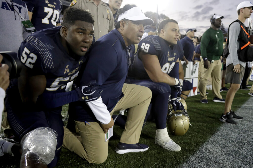 Navy head coach Ken Niumatalolo, center, kneels with players during a game on Saturday, Oct. 5, 2019.
