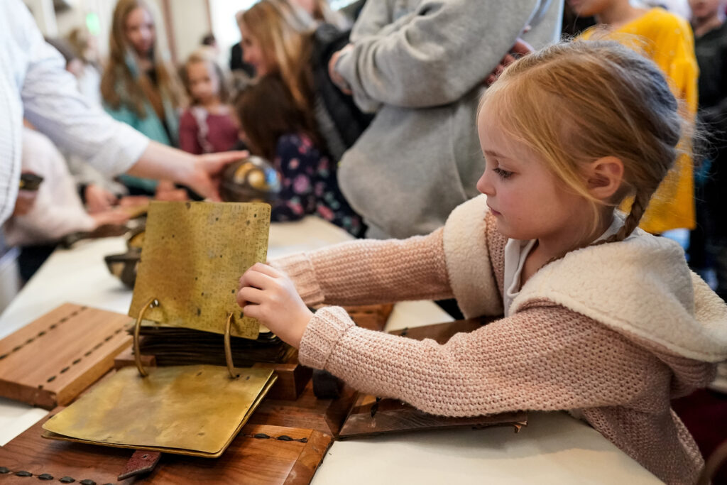 Zoe Moss, 5, of Tooele, Utah, checks out props from the Church's Book of Mormon Videos, including the Large Plates of Nephi, after a screening in the Joseph Smith Memorial Building Legacy Theater in Salt Lake City on Saturday, Dec. 7, 2019.