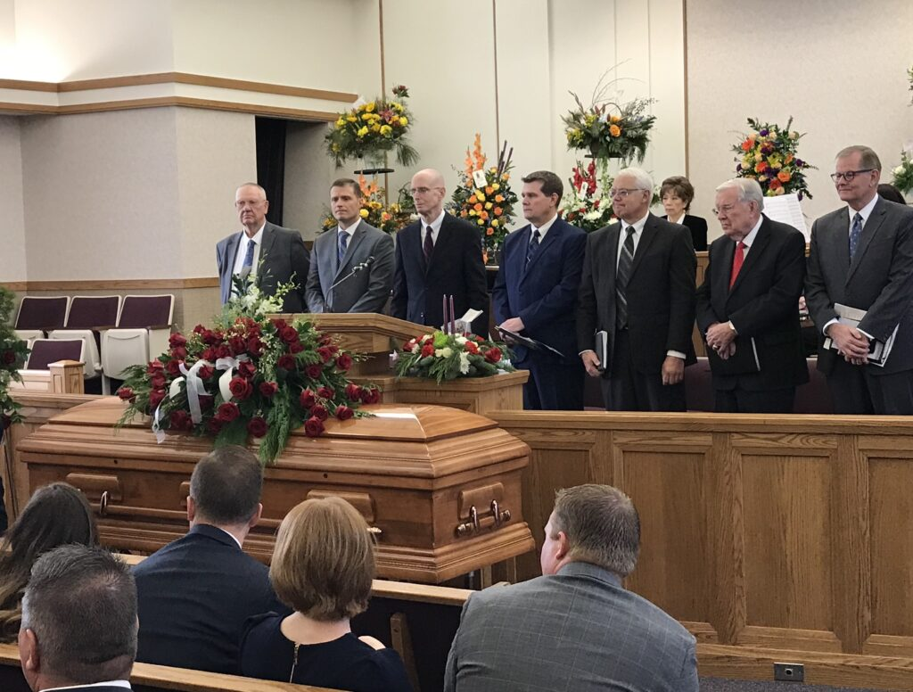 President M. Russell Ballard and Elder Gary E. Stevenson, far right, join other local Church leaders on the stand prior to the Dec. 18, 2019., funeral service for James D. Hansen, Sr., in Ammon, Idaho. Brother Hansen was the patriarch of the Hansen family that lost nine members in November, 2019, to a private plane crash.