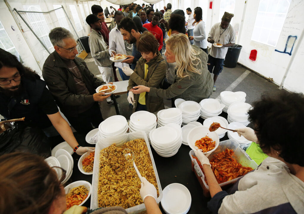 Members of The Church of Jesus Christ of Latter-day Saints help feed the refugees at Baobob refugee camp in Rome, Italy, on Monday, April 16, 2018. Latter-day Saint Charities contributes volunteers, dining tents, and money to the organization.