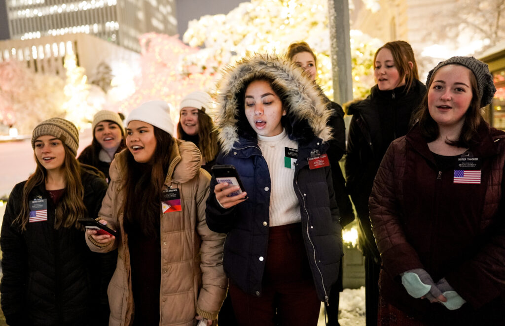 Missionaries for The Church of Jesus Christ of Latter-day Saints sing Christmas carols as people enjoy the first night of the annual Christmas lights display at Temple Square in Salt Lake City on Friday, Nov. 29, 2019.