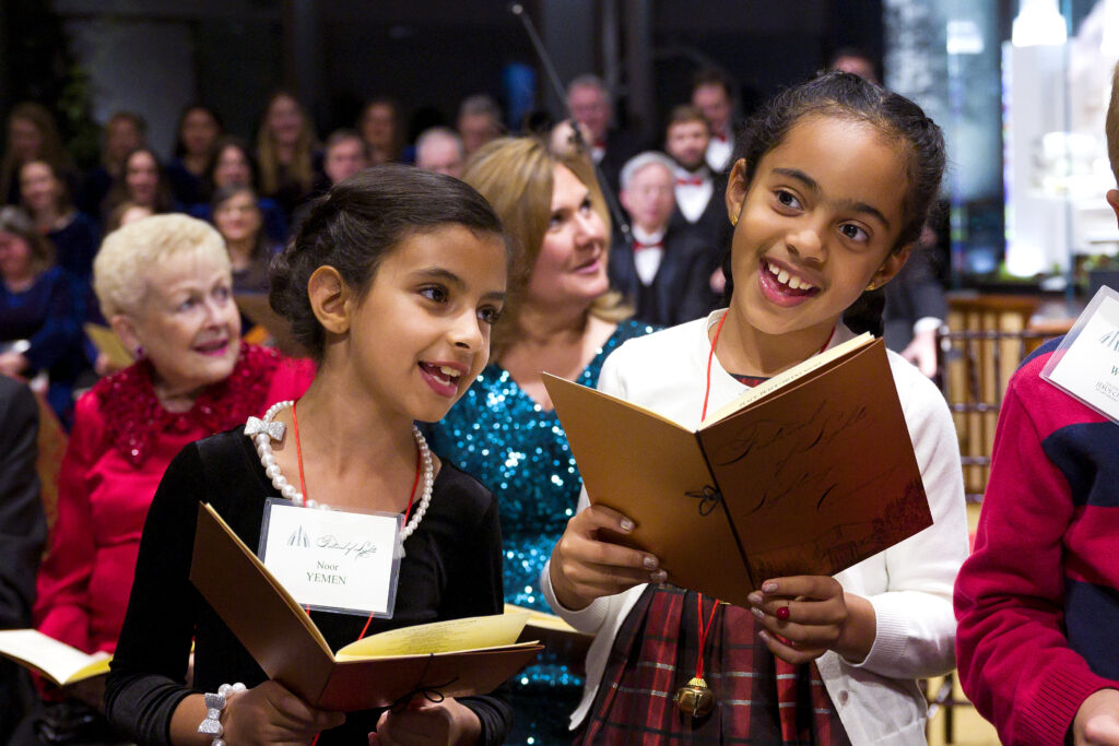The daughter of the Ambassador of Yemen and the granddaughter of the Ambassador of Oman sing Christmas carols at the Dec. 3, 2019, opening ceremonies of the Festival of Lights at the Washington D.C. Temple Visitors' Center.