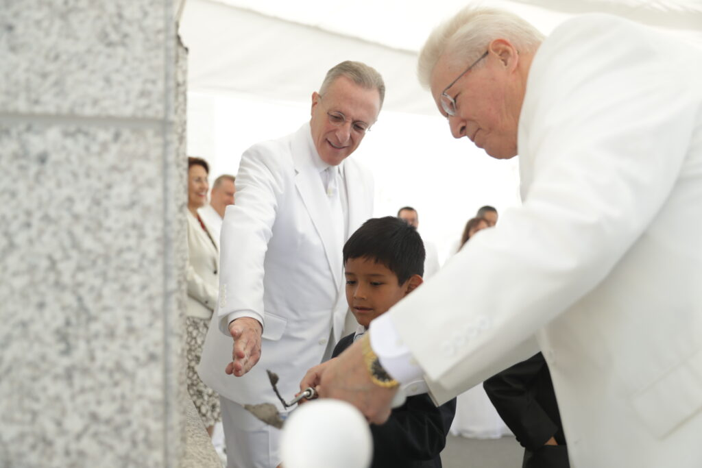 Elder Ulisses Soares, left, and Bishop Dean M. Davies assist a little boy in placing mortar on the capstone of the Arequipa Peru Temple on Dec. 15, 2019.