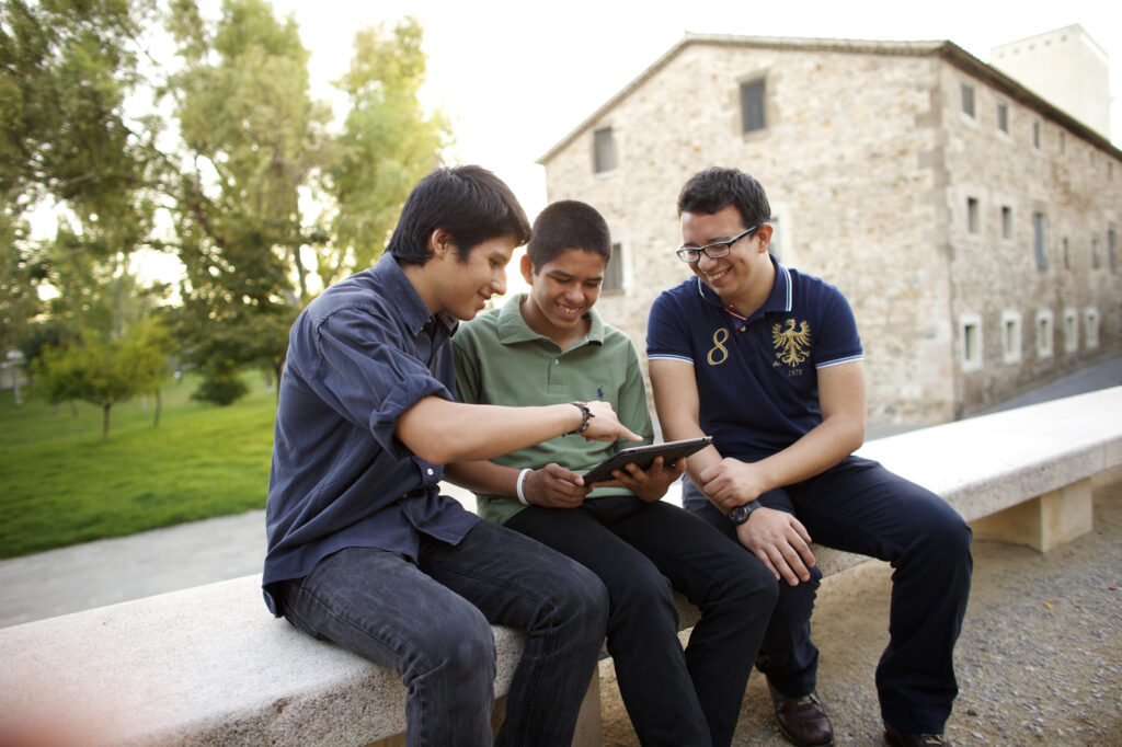 Three young men share a tablet together. A new FamilySearch blog resource features quick and easy ways for youth to get involved in family history.