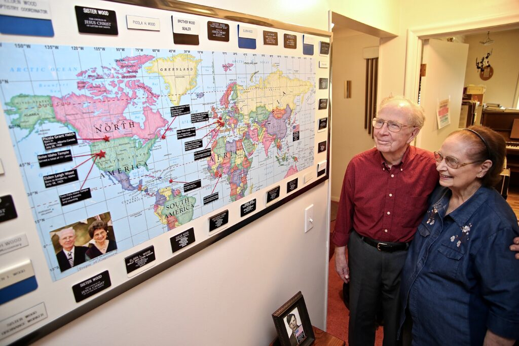 Elden Wood stands next to a map in his home which marks his years of service in the Church with his wife, Picola Wood, including seven full-time missions (six together) and their service in various temples.