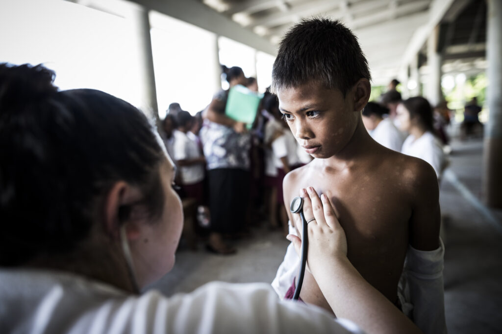A student from BYU checks the heart of a child from a primary school in Samoa to screen for rheumatic heart disease.