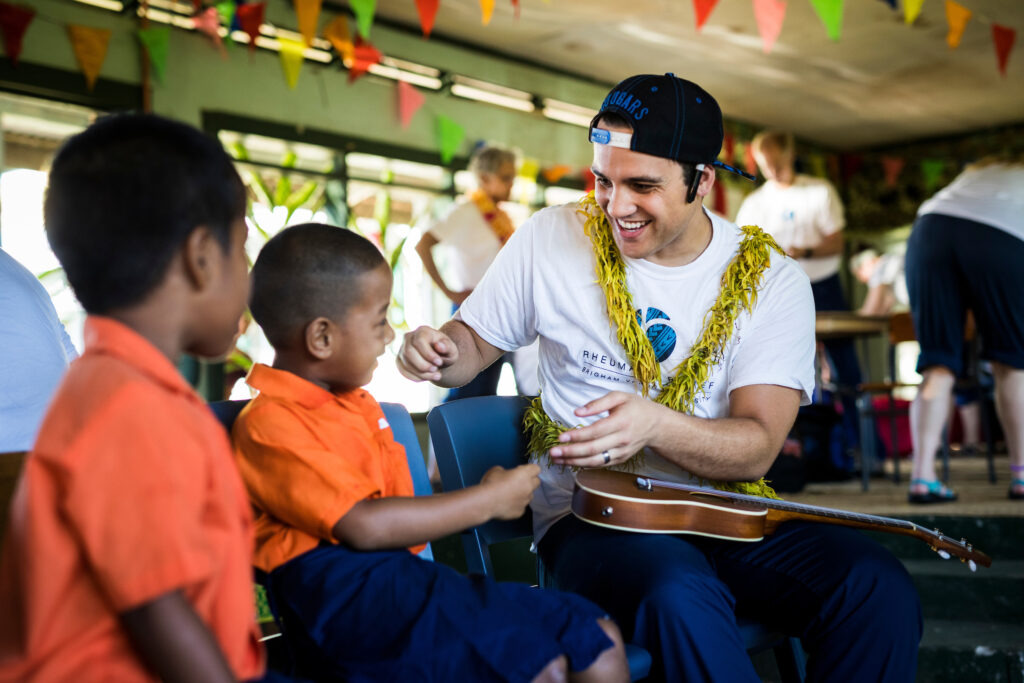 A BYU student volunteer examines a Samoan boy as part of the Rheumatic Relief program.