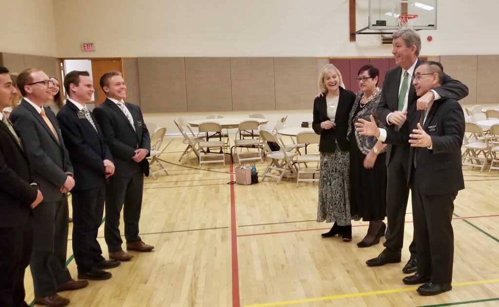 Elder S. Gifford Nielsen puts his arm around the shoulder of Canada Calgary Mission President Stephen A. Keung in front of missionaries who had welcomed them in song to a series of mission tour meetings on Oct. 31, 2019, in Calgary, Alberta, Canada.