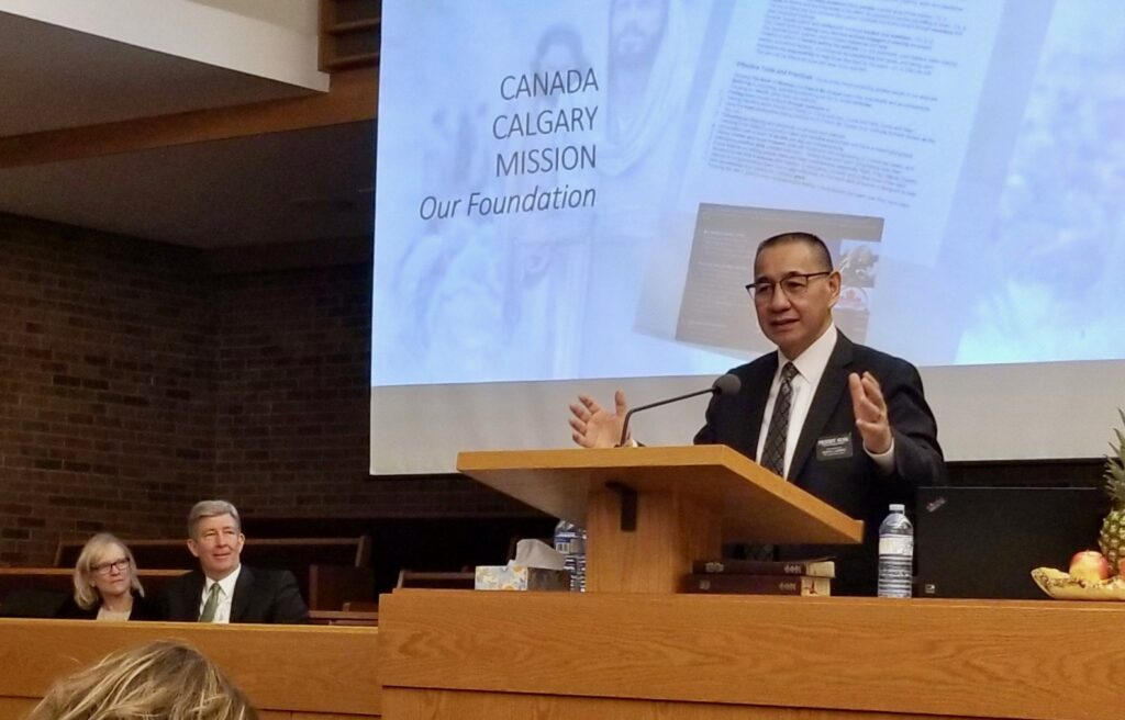President Stephen A. Keung of the Canada Calgary Mission speaks to his missionaries during a mission tour meeting on Oct. 31, 2019, in Calgary, Canada, while Sister Wendy Nielsen and Elder S. Gifford Nielsen look on.