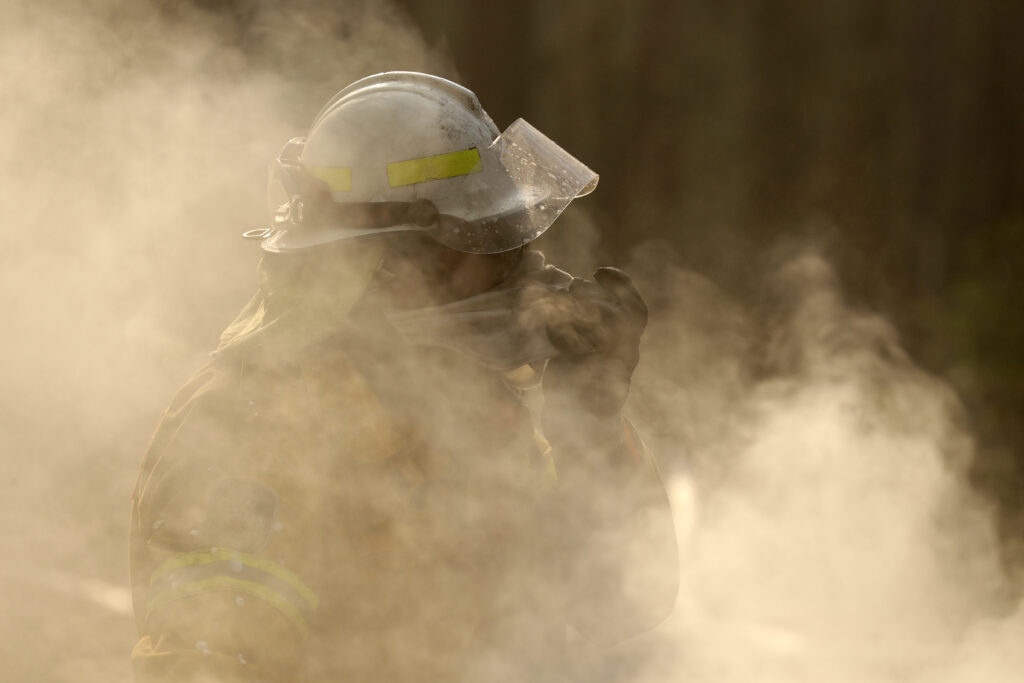 A firefighter covers his face from block smoke as he battles a fire near Bendalong, Australia, Friday, Jan. 3, 2020.