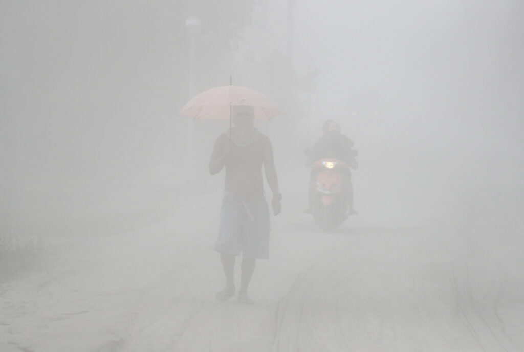 A man walks through a cloud of volcanic ash as he evacuates to safer grounds as Taal volcano in Tagaytay, Cavite province, southern Philippines on Monday, Jan. 13, 2020. Red-hot lava is gushing from the volcano after a sudden eruption of ash and steam that forced residents to flee and shut down Manila's airport, offices and schools.