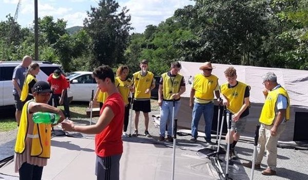 """Members and missionaries in """"Helping Hands"""" vests assemble canopies to be used by people displaced by Puerto Rico earthquakes."""