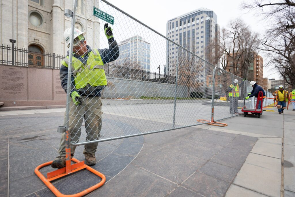 Workers put up a fence around the Salt Lake Temple as renovation gets underway on Temple Square in Salt Lake City.
