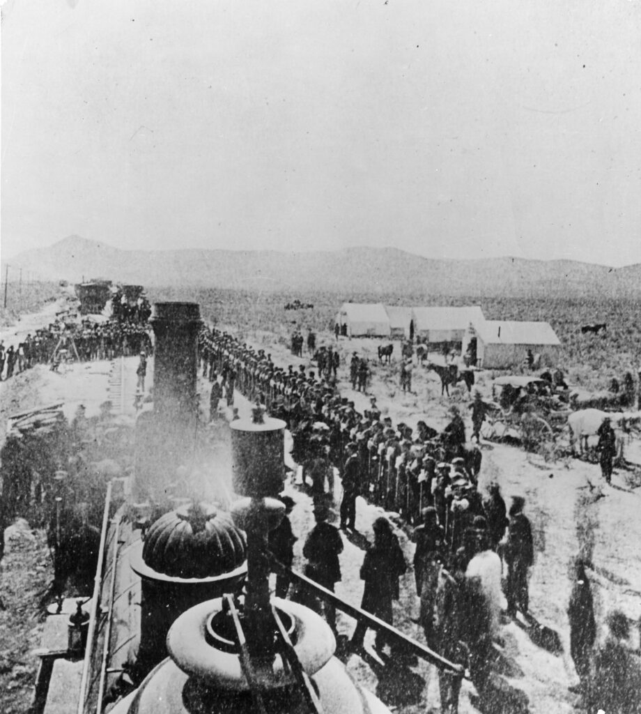 "A view at Promontory, Utah, May 10, 1869, during the ""Last Spike"" ceremony when rails of the Central Pacific (now Southern Pacific) and the Union Pacific were joined to complete the first transcontinental railroad. The picture is taken from the U.P. locomotive #119, looking westward, and shows the four companies of the 21st Infantry in formation alongside the track Central Pacific's locomotive, ""Jupiter,"" with tent-buildings."