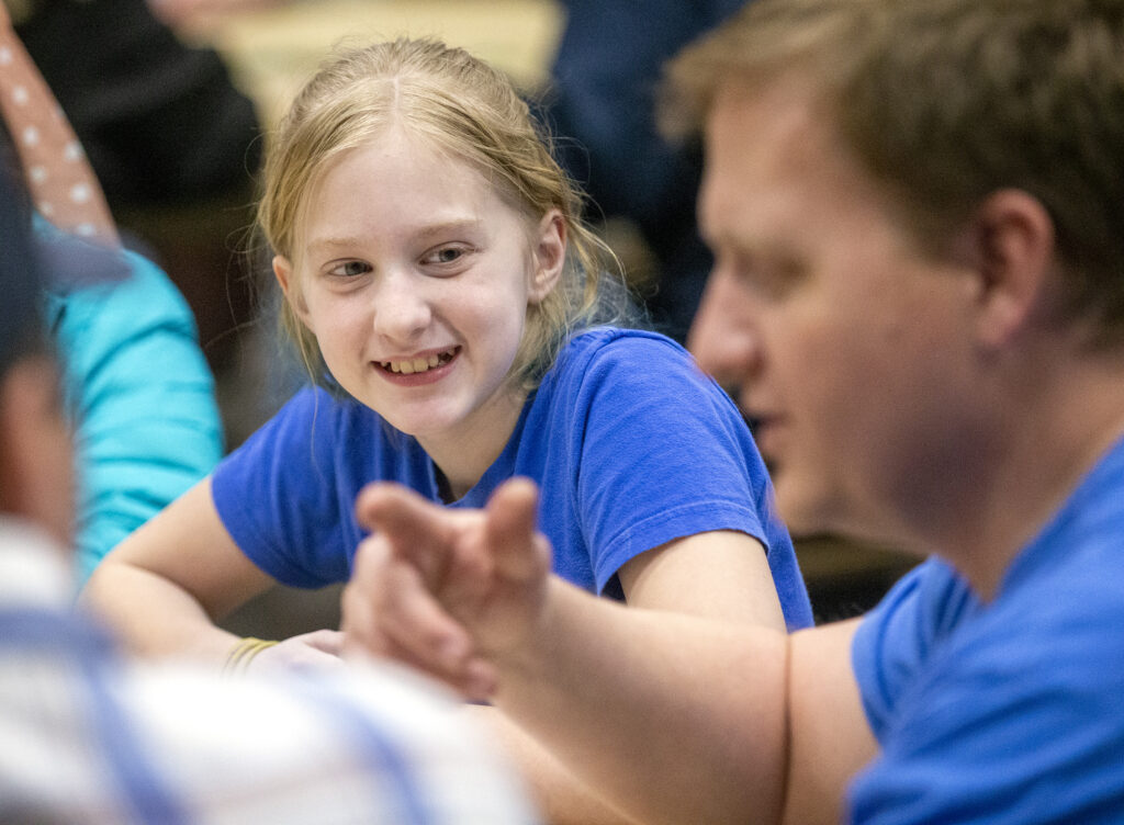 Gwen Buehner smiles at Dave Hansen, a priests quorum specialist, as he talks while youth and leaders in the Willow Creek 6th Ward, Sandy Utah Willow Creek Stake of The Church of Jesus Christ of Latter-day Saints gather to play games together on Wednesday, Jan. 22, 2020.