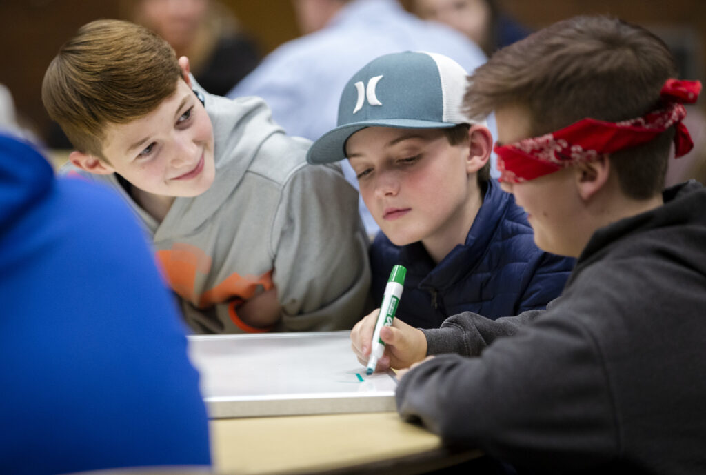 Tyler Nobis and Ryan Hill watch as Redding Egan draws a picture while blindfolded as youth in the Willow Creek 6th Ward, Sandy Utah Willow Creek Stake of The Church of Jesus Christ of Latter-day Saints gather to play games together on Wednesday, Jan. 22, 2020.