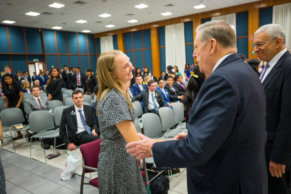 Elder Jeffrey R. Holland greets a sister missionary during meeting in Lima, Peru.