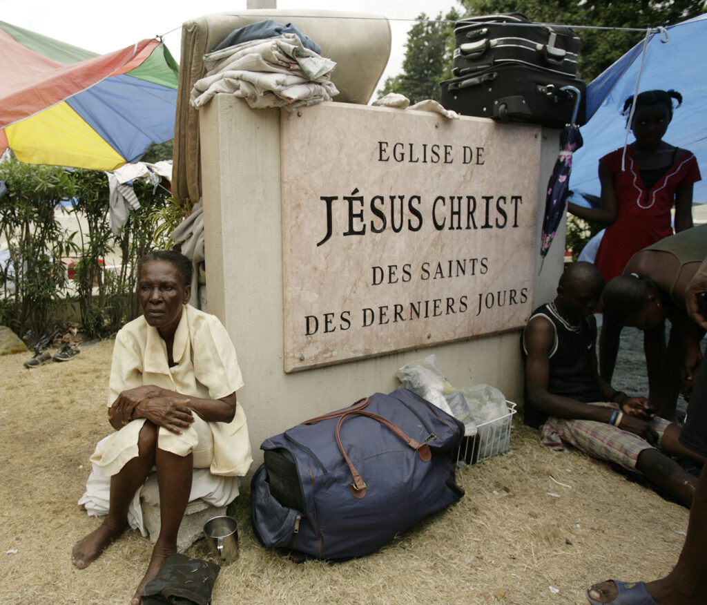 Marie Terez Antenor sits by the Centrale Ward meetinghouse sign where her family is temporarily living in Port-au-Prince, Haiti, on Jan. 26, 2010, following the Jan. 12 earthquake.