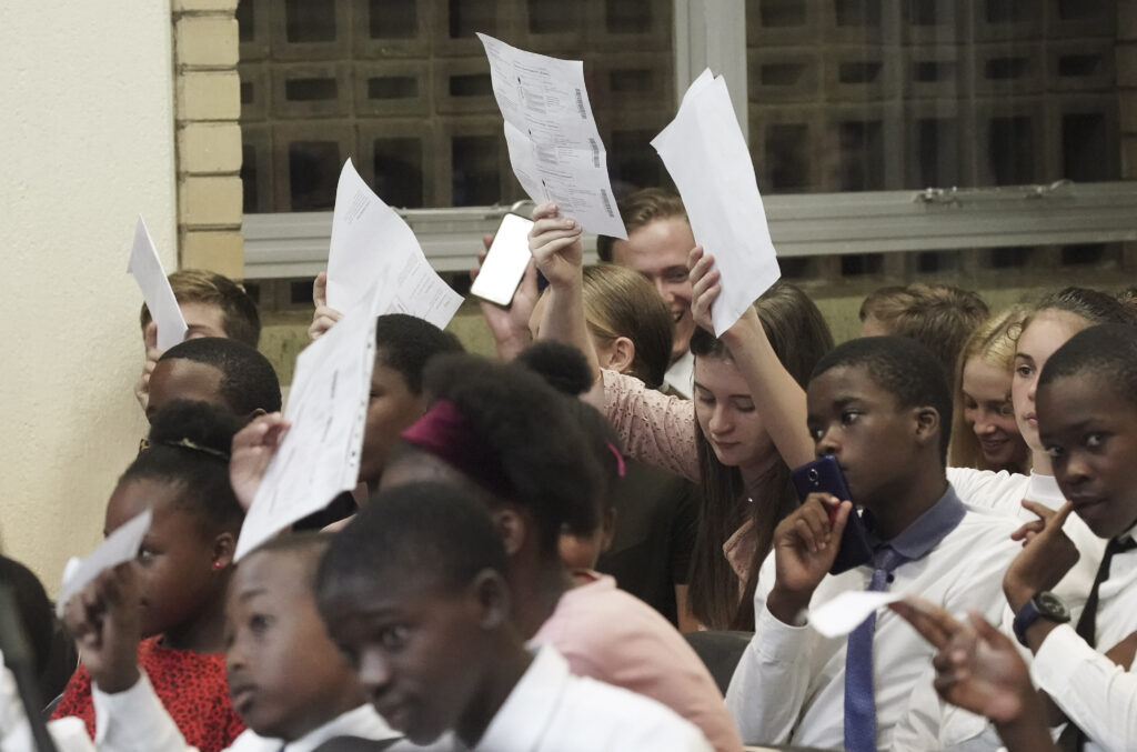 Youth hold up their family history names as Elder Ronald A. Rasband, of The Church of Jesus Christ of Latter-day Saints' Quorum of the Twelve Apostles, speaks during a Durban South Africa Temple youth devotional in Durban, South Africa, on Saturday, Feb. 15, 2020.