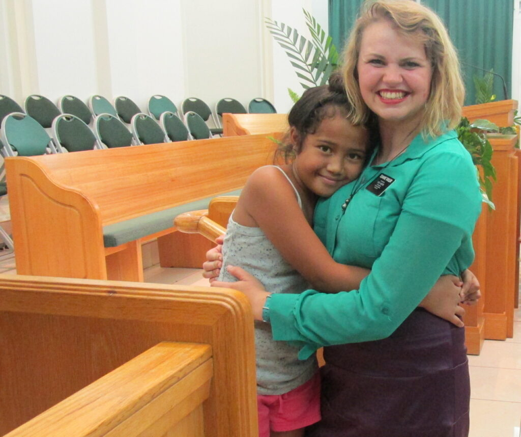 Sister Morgan Taylor embraces a young friend during her service in the Tahiti Papeete Mission.