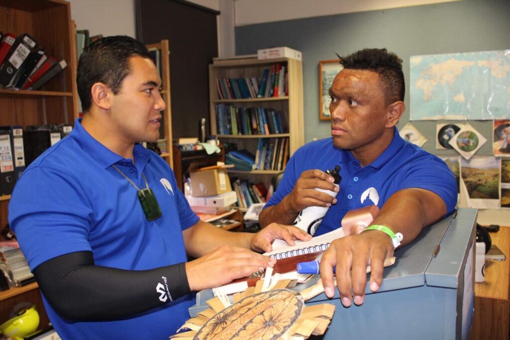 Awanui Morris, left, speaks with another young single adult counselor in New Zealand.