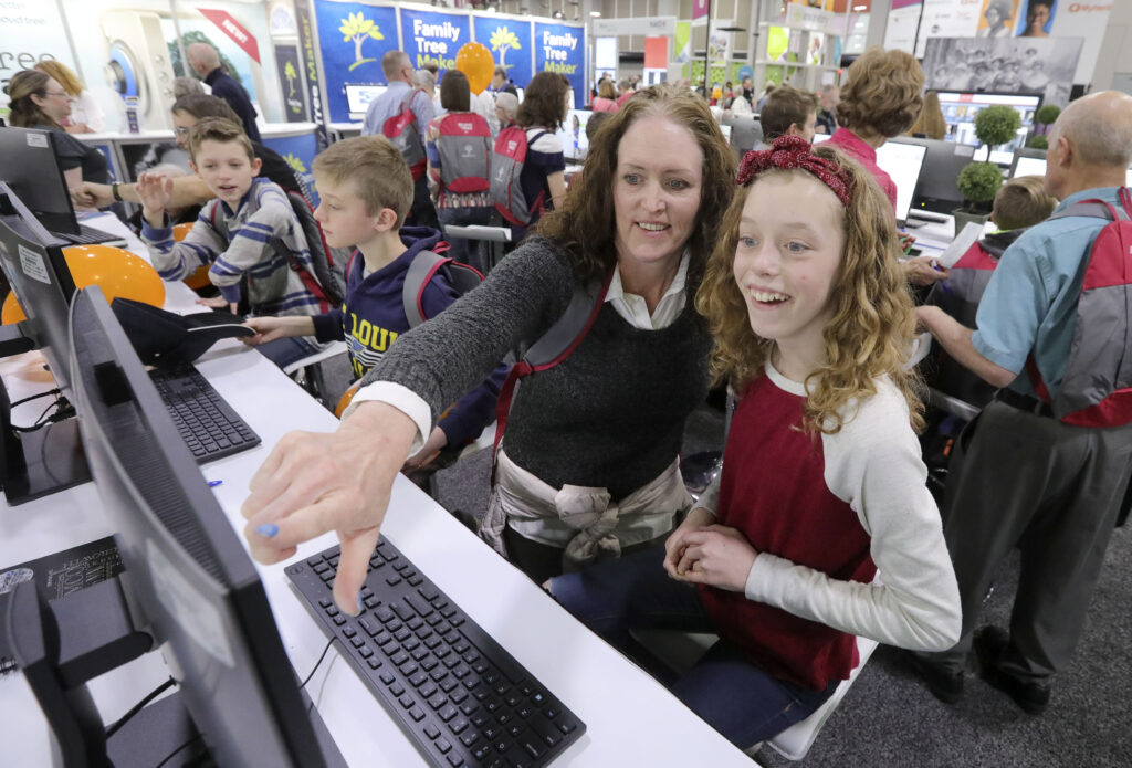 Melanie Gibby and her daughter, Anna Gibby, use Compare-a-Face to see what famous people and ancestors Anna looks like at the FamilySearch booth during RootsTech at the Salt Palace Convention Center in Salt Lake City on Feb. 29, 2020.
