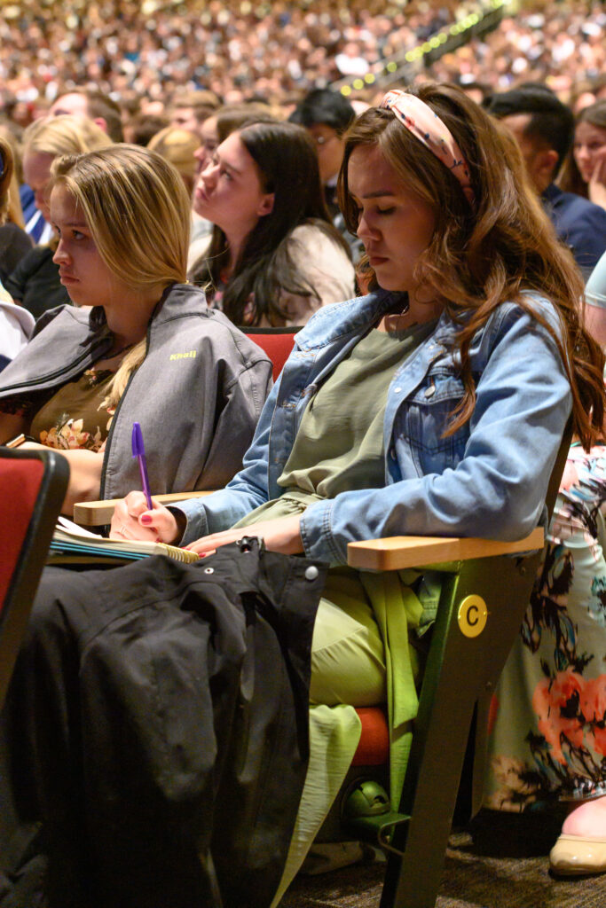 A young woman takes notes during a devotional with Elder Dieter F. Uchtdorf of the Quorum of the Twelve Apostles and his wife, Sister Harriet Uchtdorf, at BYU-Idaho on March 1, 2020.