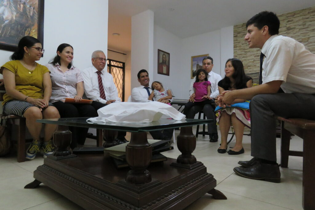 The Trochez Family gathers for a home sacrament service in Cali, Colombia, on March 15, 2020. Traditional gatherings were cancelled because of the coronavirus pandemic.