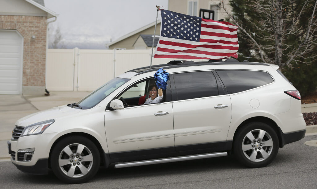 """A well wisher waves as friends and neighbors welcome home full-time missionaries during a """"driving tour"""" in South Jordan, Utah, on Thursday, March 26, 2020."""
