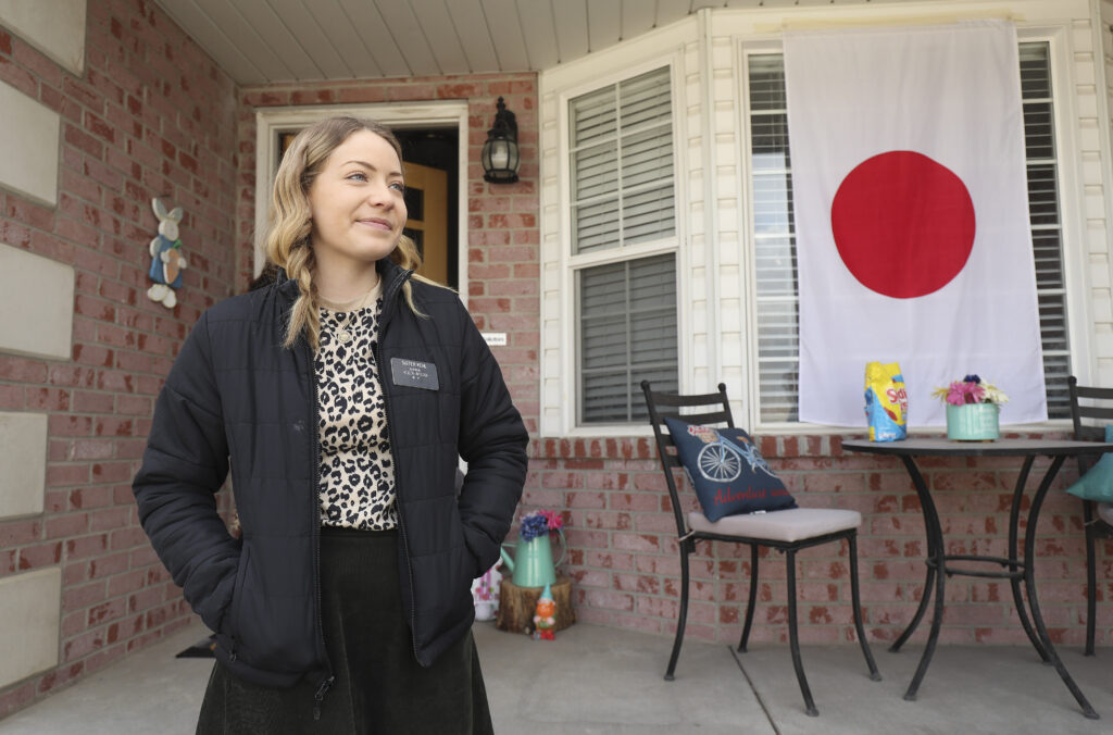 """Sister Madison Kehl waits as friends and neighbors welcome home full-time missionaries during a """"driving tour"""" in South Jordan, Utah, on Thursday, March 26, 2020."""
