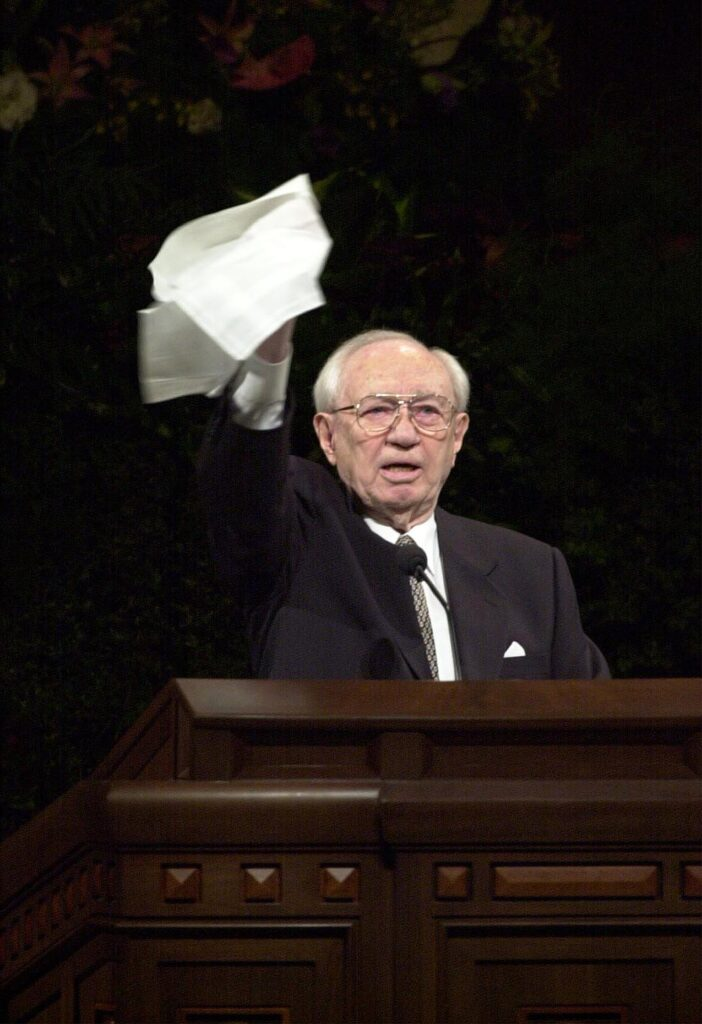 President Gordon B. Hinckley demonstrates to the congregation during the October 2000 general conference how to give the Hosanna Shout.
