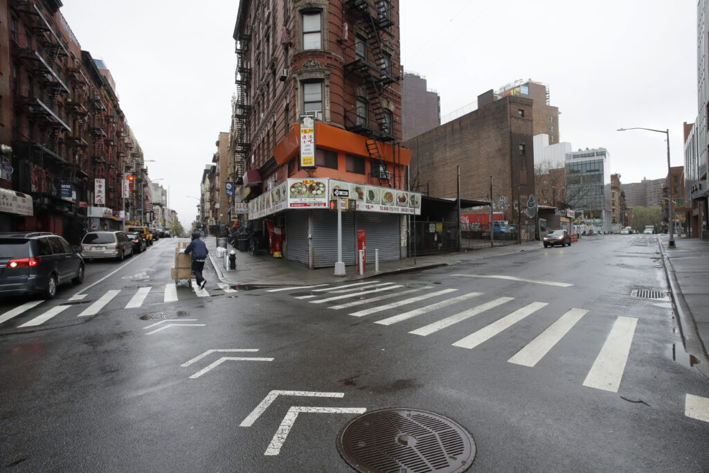 A man pushes a cart of boxes through the intersection of Eldridge St. and Division Street, Monday, April 13, 2020 in New York's Chinatown during the coronavirus pandemic. The streets are normally bustling with vehicles and pedestrians.