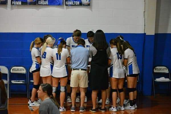 Sister Megan Sintay, middle right, prays with the Wilcox Academy girls' volleyball team prior to a match in fall 2019.