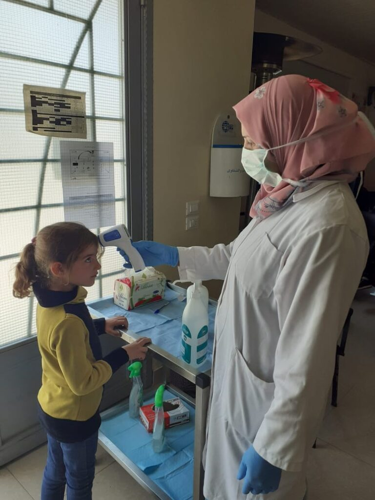 A girl has her temperature checked in Lebanon, where Latter-day Saint Charities is working with international medical nonprofit MedGlobal to provide medical supplies to prevent the spread of COVID-19.