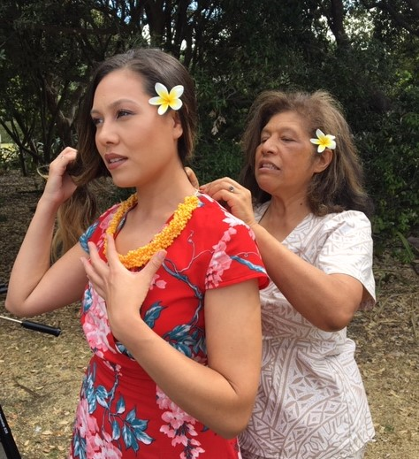 "Lissa Huysmans, a Latter-day Saint choir member, helps Ericca Huysmans, her daughter and director of the choir, with the final touches on her traditional Niuean dress prior to recording the hymn, ""We Thank Thee, O God, for a Prophet."" Church members from six different continents, including New Zealand, virtually joined The Tabernacle Choir on Temple Square during the April 2020 General Conference."