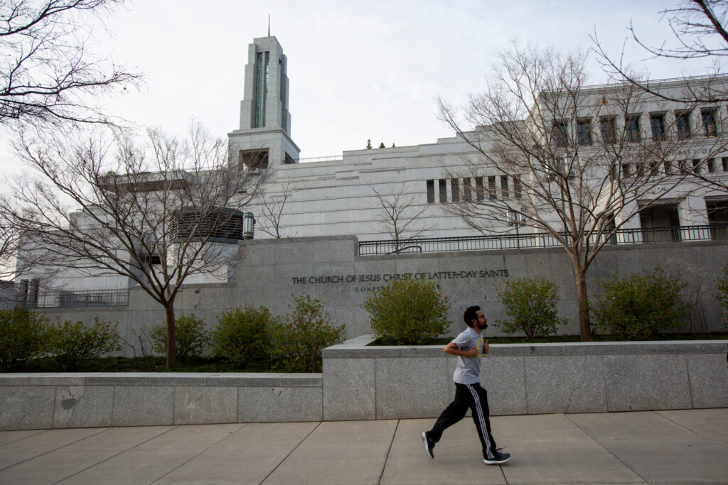 A man jogs past an empty Conference Center during the evening session of the 190th Annual General Conference in Salt Lake City on Saturday, April 4, 2020.