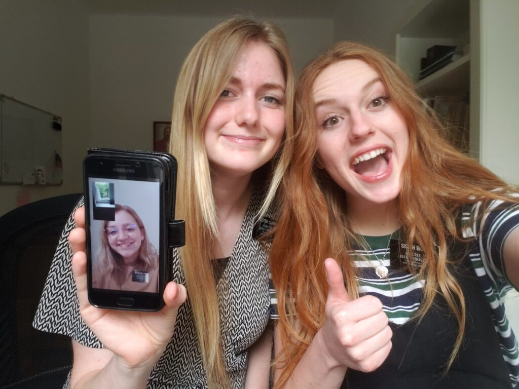 Sister Halsey Curry, left, and Sister Kylie Bice, right, are joined by Sister Victoria Nielson, on screen, who returned home to Canada from the MTC to await reassignment. Sister Nielson joins the Berlin missionaries for Sunday devotional and team-teaches with Sisters Curry and Bice over WhatsApp.