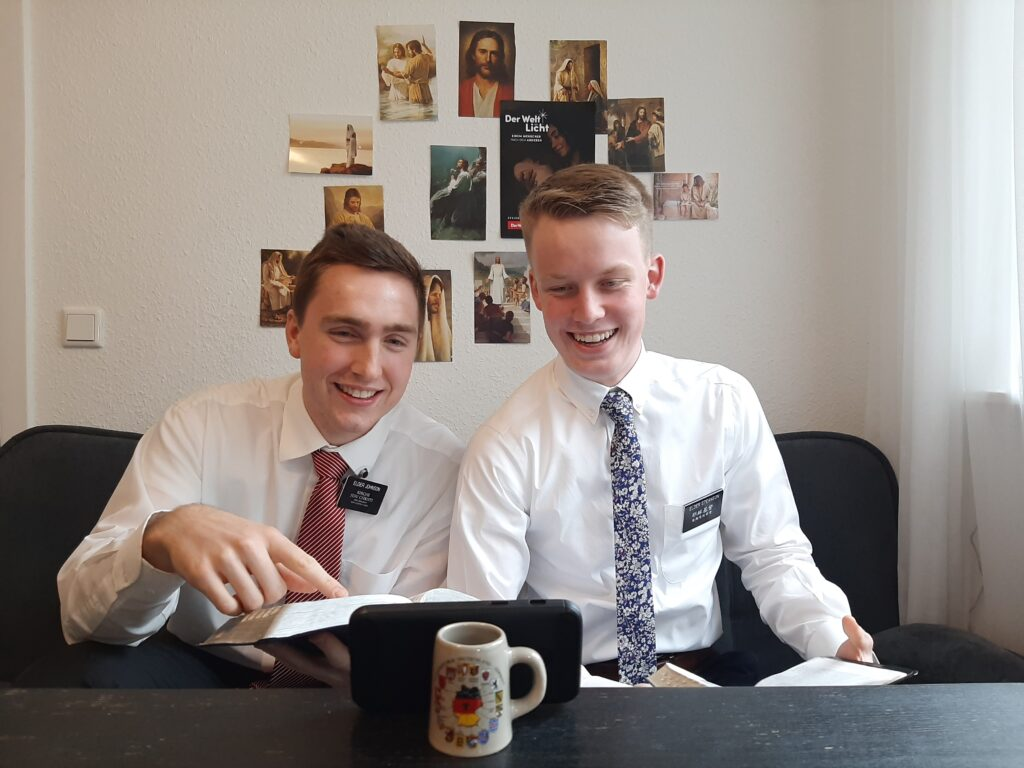 Elders Ezra Johnson, left, and Harrison Steanson of the Germany Berlin Mission are using their smartphone to teach via video, texts and calls over several time zones and several different languages from their Hanover, Germany, residence in May 2020.